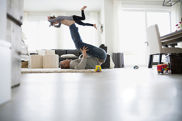 Father flying daughter on feet in living room